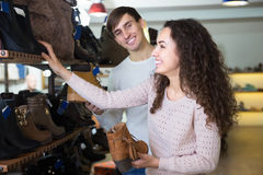 Young couple buying winter shoes. Smiling young couple buying winter shoes in a shoe store royalty free stock photography