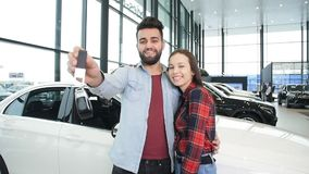 A young happy couple buys a new car. Smiles and shows the keys