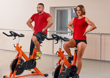 Young couple bycicle cycling in gym Stock Photography