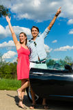 Young couple with cabriolet in summer on day trip Stock Image