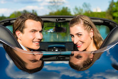 Young couple with cabriolet in summer on day trip. Young hip couple - man and woman - with cabriolet convertible car in summer on a day trip stock photos