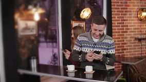 Young couple in cafe browsing internet on smart phone. Young happy couple with smartphone in cafe stock footage