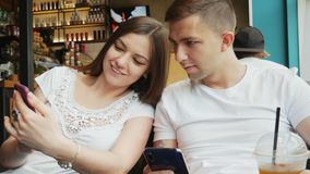 Young couple in a cafe, girl shows a man a photo or a new application on a mobile phone stock footage