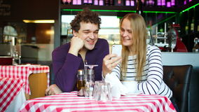 Young couple in cafe having a video chat on. Happy young man and woman in cafe having video chat using smartphone stock footage