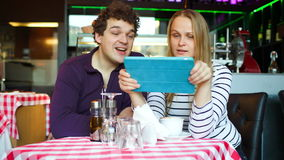 Young couple in cafe having a video chat on tablet. Excited young man and woman chatting on touchpad in cafe stock footage