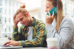 Young couple in cafe with laptop and mobile phone, confused man and woman talking on the phone. Young couple in cafe with laptop and mobile phone, confused men Stock Photo