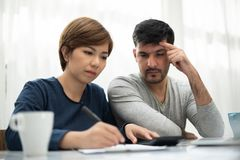 Young couple calculating their budget for new house. Stressed Young couple calculating their budget for new house royalty free stock photography
