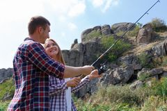 A young couple came on a fishing trip to catch fish for dinner. Fishing together on a beautiful background. Stock Photos