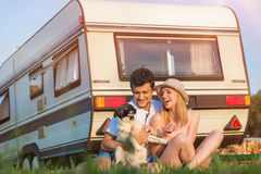 Young couple with a camper van. Beautiful young couple in front of a camper van on a summer day royalty free stock photos