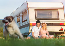Young couple with a camper van. Beautiful young couple in front of a camper van on a summer day Royalty Free Stock Photo