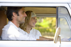Young couple in camper van, man driving, smiling, side view Stock Image