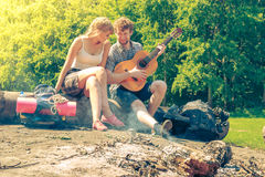 Young couple camping playing guitar outdoor Stock Photos