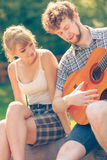 Young couple camping playing guitar outdoor Stock Photo