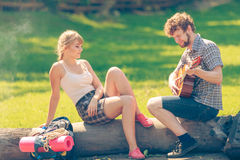 Young couple camping playing guitar outdoor Royalty Free Stock Image