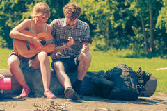 Young couple camping playing guitar outdoor. Adventure, tourism, enjoying summer time together - young couple tourists having fun playing guitar in camping royalty free stock images
