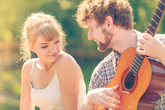 Young couple camping playing guitar outdoor Royalty Free Stock Photo