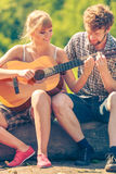 Young couple camping playing guitar outdoor Stock Images
