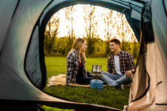 Young couple camping. Shot of a happy couple camping on the nature and cooking Stock Image