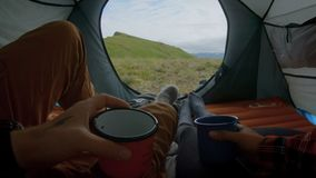 Young couple camps out in tent. POV of young couple enjoying coffee from hiking travelling mugs or cups, while cozy and cuddling inside camping tent, wear travel stock footage