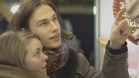 Young Couple At A Candy Store. Portrait Of A Young Couple Looking At Hanging Cookies At A Candy Store And Smiling In Slow Motion stock video footage