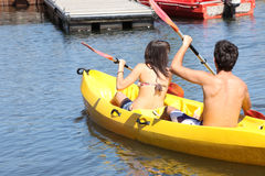 Young couple canoeing. Two teenagers canoeing on a lake royalty free stock photos