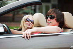 Happy young fashion couple driving a car Royalty Free Stock Images