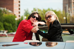 Happy young fashion couple in a convertible car Royalty Free Stock Image