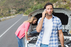 Young couple after a car breakdown Royalty Free Stock Photo