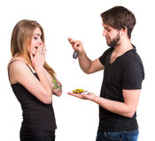 Young couple with car keys and miniature cars Royalty Free Stock Images