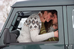 Young couple in car in snow. Embracing stock photo