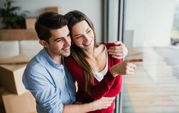 Young couple with cardboard boxes moving in a new home, looking out of window. Young happy couple with cardboard boxes moving in a new home, looking out of a stock image