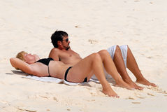 Young couple on Caribbean beach. Young couple lying on white sandy beach in Caribbean Royalty Free Stock Photo