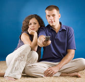Young couple on carpet with remote control Stock Photos