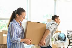 Young couple carrying box indoors. Moving into new house royalty free stock image