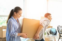 Young couple carrying box indoors. Moving into new house stock photo