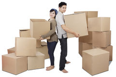 Young couple carrying boxes in studio Royalty Free Stock Images