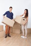Young couple carrying cardboard boxes at new home Royalty Free Stock Image