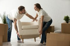 Young couple carrying chair together, placing furniture in new h. Young couple carrying chair together, house improvement, modern furniture in new home concept Stock Image