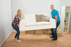 Young Couple Carrying Couch Royalty Free Stock Photography