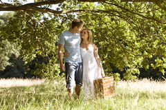 A young couple carrying a picnic basket Stock Photos