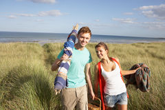 Young Couple Carrying Picnic Basket And Windbreak. Walking Through Dunes Royalty Free Stock Photos