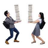 Young couple carrying a pile of books Royalty Free Stock Photos