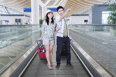 Young couple carrying suitcase on the escalator Stock Images