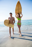 Young couple carrying surfboard at beach Stock Images