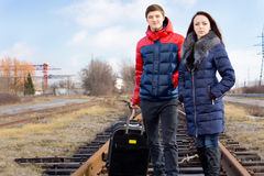 Young couple with a case waiting for the train Royalty Free Stock Images