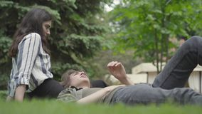 Young couple in casual clothes spending time together outdoors, having date. The girl sitting on the grass, her stock video