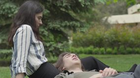 Young couple in casual clothes spending time together outdoors, having date. The girl sitting on the grass, her stock video footage
