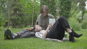 Young couple in casual clothes spending time together outdoors, having date. The guy sitting on the blanket on the grass stock video footage