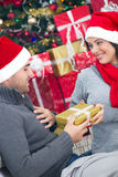 A young couple celebrate Christmas night. Girl surprising a boy with a gift in Christmas night stock photography