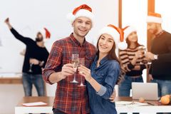 A young couple celebrates at a corporate celebration. They hold glasses with champagne in their hands. They have Santa Claus hats on their heads Royalty Free Stock Image